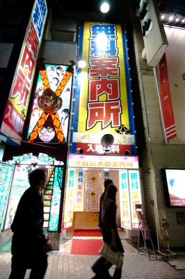 "Pedestrians pass a ""free information center"" on Shibuya's Dogenzaka."