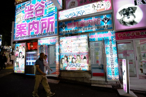 "Two men walk past a ""free information center"" on Shibuya's Dogenzaka. The sign advertises aroma relaxation, ¥4,000 for 40 minutes."