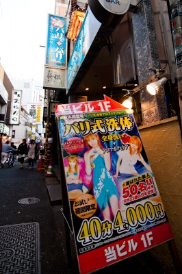 "A sign advertising a ""Bali-style body wash"" by Japanese girls with an average age of 23, ¥4,000 for 40 minutes."