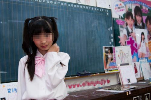 """A 10-year-old """"junior idol"""" poses for a photo at a bookshop in Akihabara. Fans who buy a girl's DVD get complementary tickets to events where they can meet the idols and take their photos. Photo by Sarah Noorbakhsh"""
