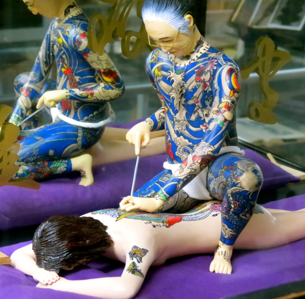 Another figurine found at the Tattoo Museum, featuring Horiyoshi III working on the body of a woman