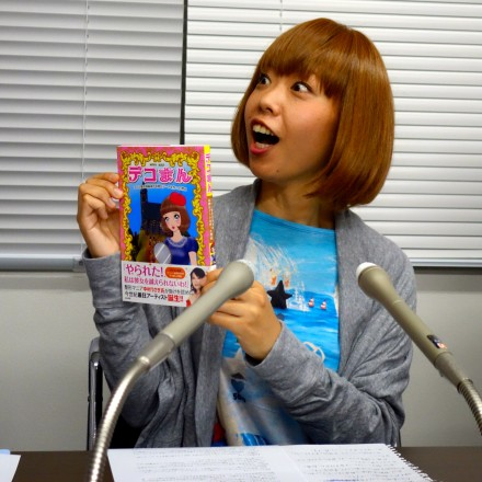 The artist Rokudenashiko holds up the comic book she wrote explaining why she makes art about female genitalia & her own vagina. (After being released from custody for obscenity charges)