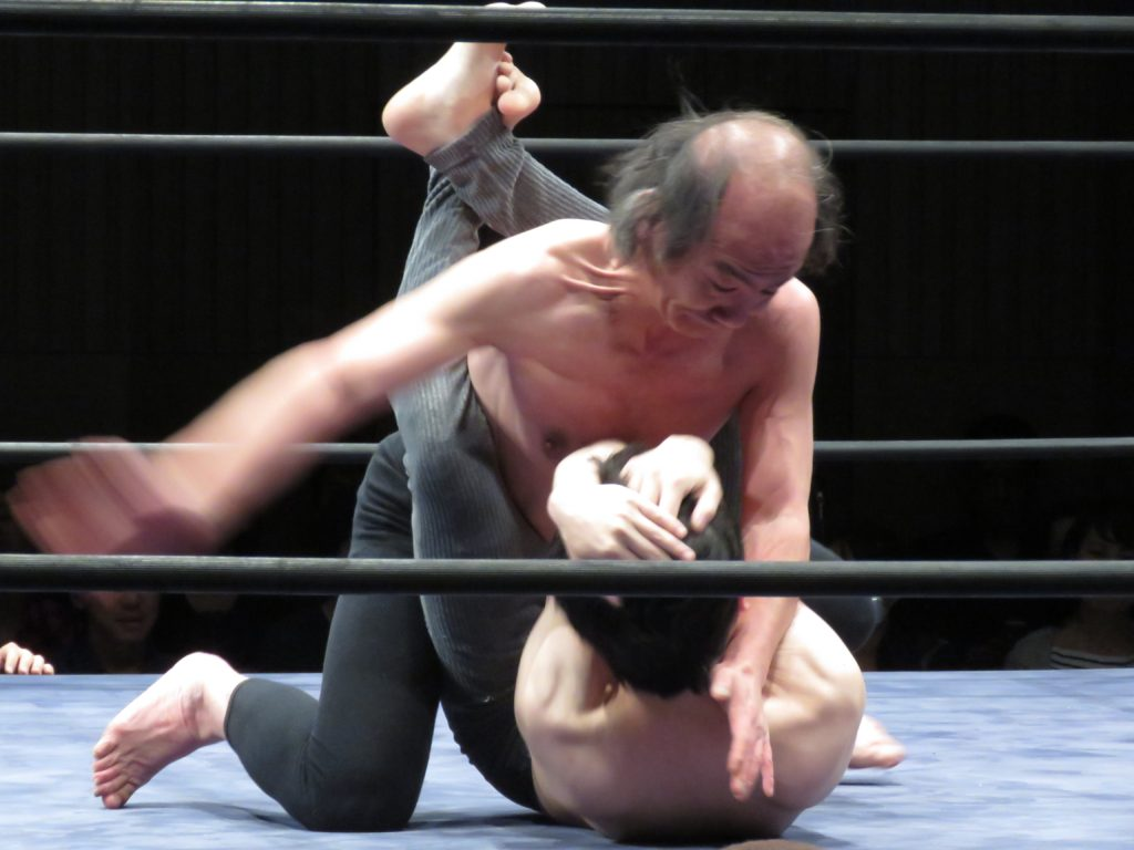 "The wrestler ""Alcoholism"" pummels his opponent, ""Worthless Goro"",  who suffers from depression during the 25th anniversary Doglegs match.  April 15th 2016, photo taken by Jake Adelstein  *Alcoholism is the older man"