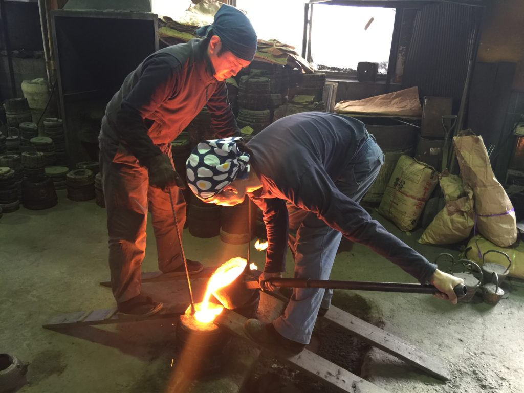 It takes two craftsmen to pour the iron into the mold